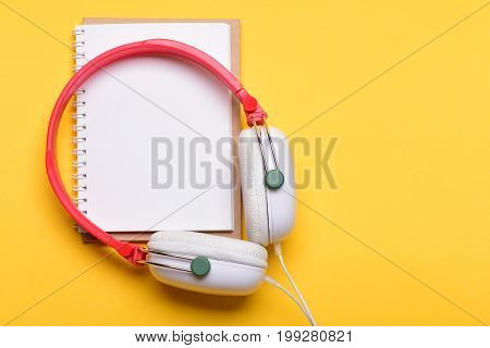 Headset for music and blank page with copy space. Headphones in white and red color with empty notebook. Music and note taking concept. Modern earphones isolated on yellow background top view