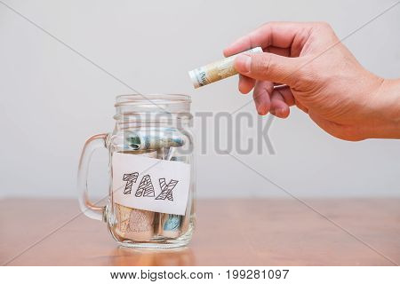 Putting money into a jar labelled tax