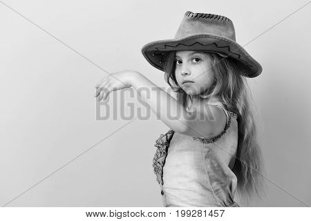 Kid With Serious Face And Long Hair Wears Jeans Dress