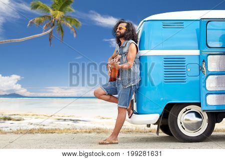 summer holidays, travel, music and people concept - young hippie man playing guitar and singing at minivan car over tropical beach background