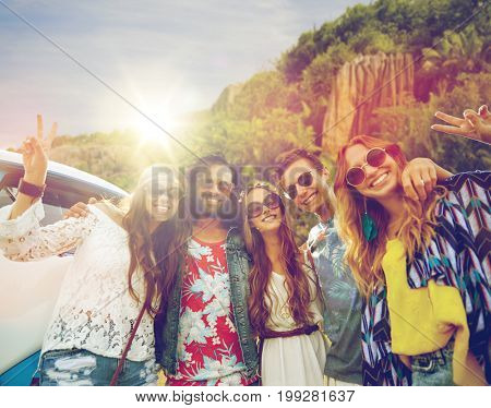 summer holidays, road trip, travel and people concept - smiling young hippie friends at minivan car showing peace hand sign over island background