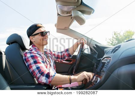 summer holidays, travel, road trip and people concept - happy young man driving convertible car with manual transmission