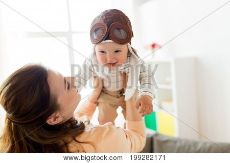family, child and motherhood concept - happy smiling young mother playing with little baby wearing pilot hat at home (focus on mother)