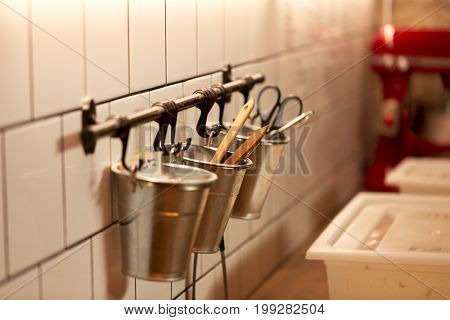 food, cooking and baking concept - bakery kitchen tools hanging on wall in buckets