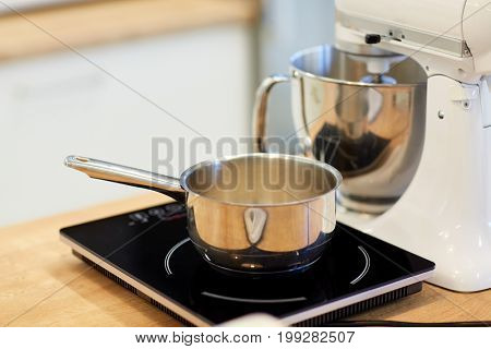 cooking, food and kitchen appliances concept - electric mixer and pot on stove