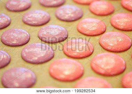 cooking, food and confectionery concept - macaron batter or meringue cream on baking paper at pastry shop