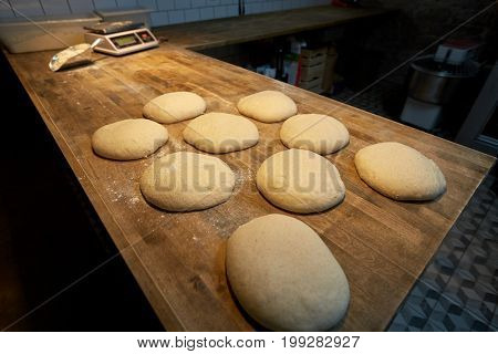 food, cooking and baking concept - yeast bread dough rising on bakery kitchen table
