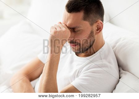 people, bedtime and rest concept - close up of stressed man in bed at home