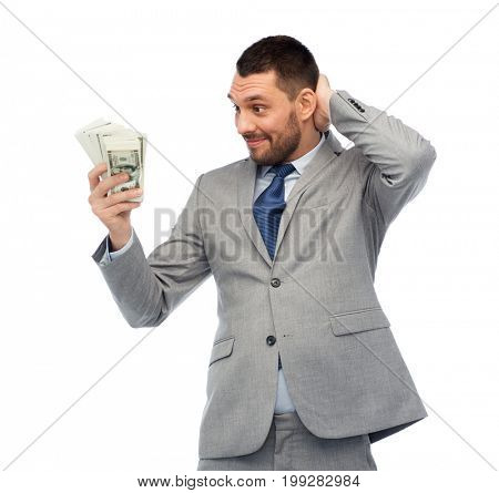 business, people and finances concept - confused businessman with bundle of american dollar cash money