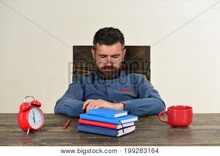 Man With Sleepy Face Sits At Wooden Table