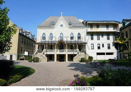 JOLIET, ILLINOIS / UNITED STATES - JULY 17, 2017: The back entrance to the Welcome Center at the University of Saint Francis features an elegant double staircase and a luxurious balcony.