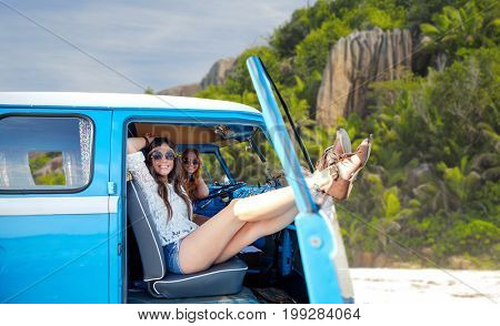 summer holidays, road trip, travel and people concept - smiling young hippie women resting in minivan car over tropical island beach background