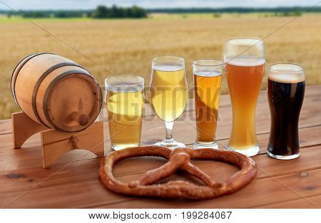 brewery, alcohol drinks and food concept - different types of beer in glasses, wooden barrel and pretzel on table over cereal field background