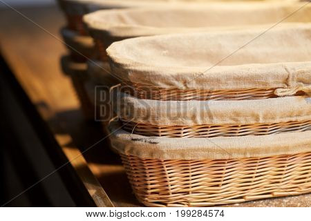 food, cooking and baking concept - bakery wicker baskets on wooden kitchen table