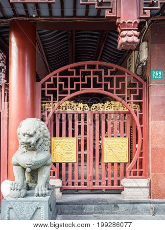 Shanghai, China - Nov 6, 2016: Guardian stone lion near the entrance to the 600-year-old Old City God Temple on Fangbang Middle Road. This gate features two large traditional Chinese seals designed in golden motifs.