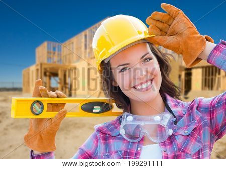 Female Construction Worker Holding Level Wearing Gloves, Hard Hat and Protective Goggles at Construction Site.