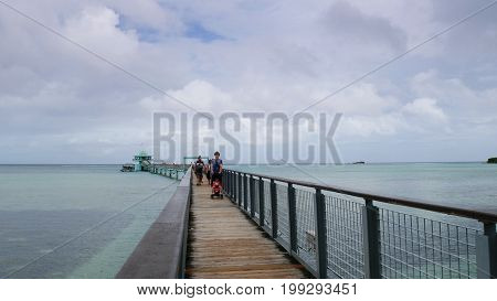 Long wooden bridge to the Fish Eye Marine Park with people walking, an underwater observatory which is one of the top attractions on Guam in a photo taken in December 2016.