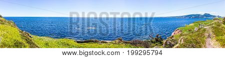 Panorama overlook of ocean cliff on trail in Bonaventure Island Quebec Canada by Perce in Gaspesie Gaspea area with green grass