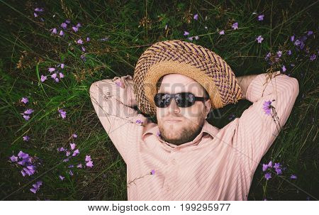 Bearded man in a straw hat and sunglasses rest on the grass among the blue bellflowers. Space for copy, vintage film filter.