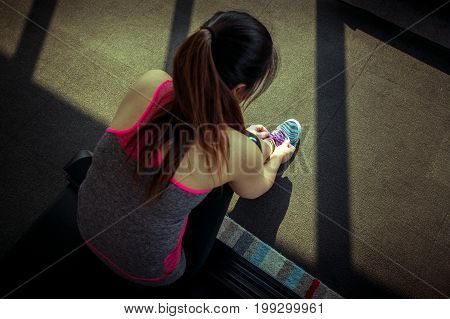 Young asian woman tying laces of running shoes preparing for jogging.