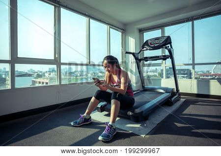 Young asian woman with mobile phone in fitness gym