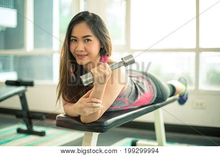 Young adult asian woman exercising with dumbbells