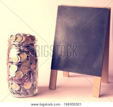 glass jar with a lot of mexican pesos coins and blackboard with vintage color tone process