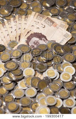 a lot of mexican pesos banknotes and coins background