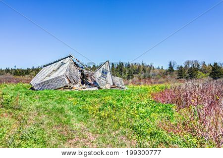 Destroyed Wooden House In Village In Summer Collapsed In Green Field