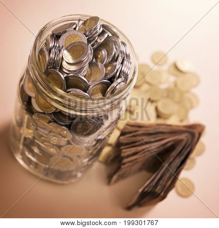 mexican pesos banknotes and coins in glass jar
