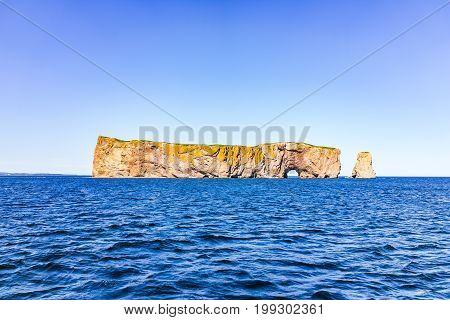Rocher Perce Rock In Gaspe Peninsula, Quebec, Gaspesie Region With Dark Blue Water