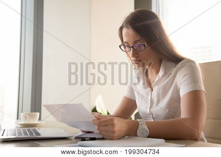Serious worried businesswoman attentively reading letter with bad news sitting at work desk, anxious woman holding document, looking at declined rejected loan application or dismissal notification