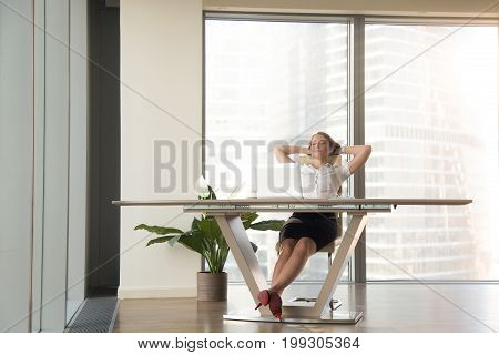 Smiling relaxed businesswoman leaning back on comfortable chair in modern luxury office, resting at desk after work hands behind head, eyes closed, employee taking a break satisfied with job done