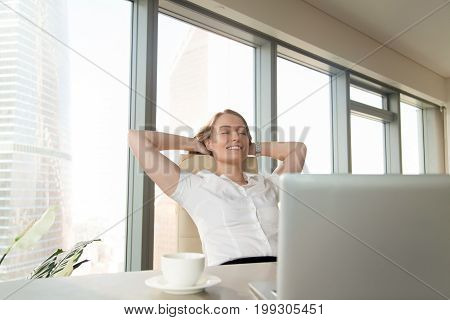 Satisfied happy businesswoman feeling relaxed sitting leaning back on ergonomic office chair, enjoying break, pleasant morning at workplace with hands behind head, eyes closed, finished all work done