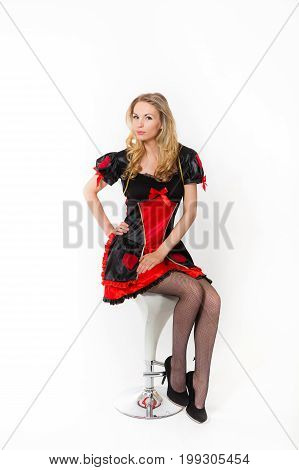 Young blond caucasian women in red dress is sitting on bar chair - Red Queen cosplay, white backgrond