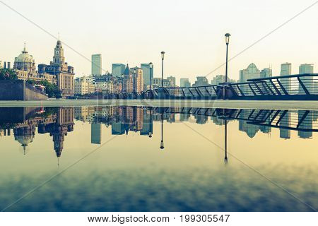 the bund skyline reflected in water puddle,shanghai,china.