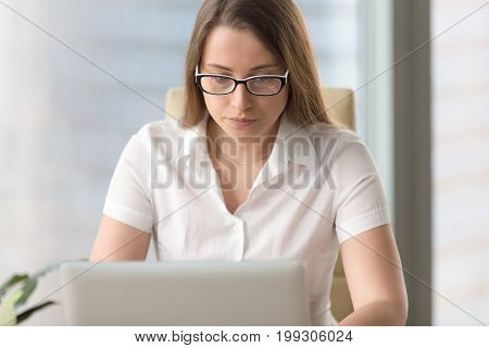 Serious worried businesswoman in glasses working on laptop, using computer, having problem error on pc, looking at screen, focused on work online, browsing internet, antivirus protection, head shot