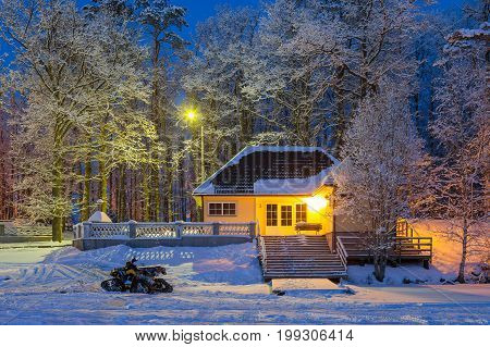 Winter story - snowmobile near cosy wooden house and frozen lake. Snowy frosty winter evening.