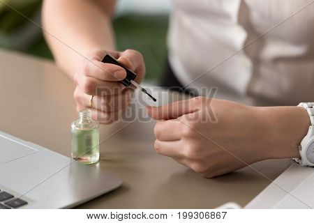 Close up view of female hands on office desk making manicure, applying lacquer, painting nails near laptop, bored lazy woman has nothing to do at work, employee misconduct in workplace, wasting time