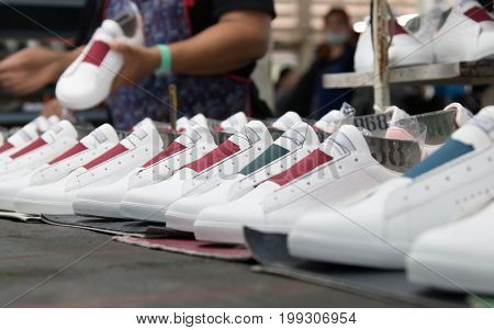 worker making white leather shoe on production line conveyor in footwear factory