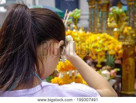 A woman praying at Erawan Temple in Bangkok Thailand. Erawan houses a statue of Phra Phrom the Thai representation of the Hindu god of creation Lord Brahma.