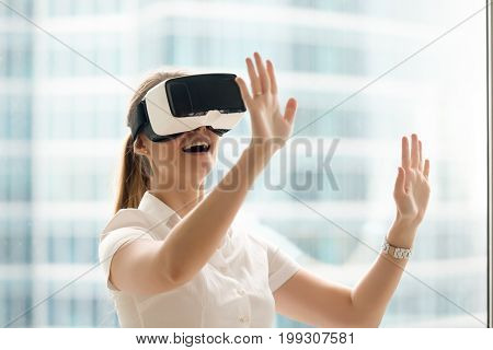 Curious amazed woman trying augmented reality glasses, feeling excited about VR headset simulation, exploring virtual life by gesturing hands to touch 3d world, having fun with goggles, head shot