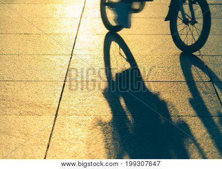 Shadow of a person riding bicycle on road.