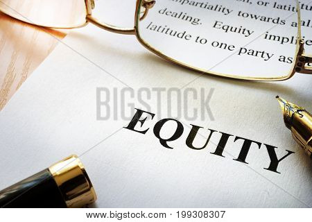 Page with word equity and a pen.