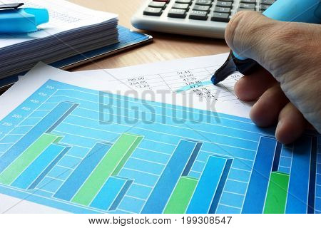 Auditor is underlined financial data in a business report.