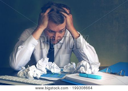 Scared business man looking on crumpled office paper. Stress and paperwork.