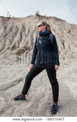 Young woman-hiker near sand hills in the desert at sunny day