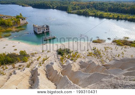 Sand quarry with a pond and abandoned prison in Rummu, Estonia