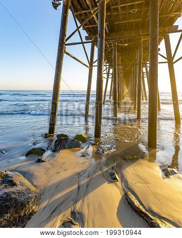Sunset at the Oceanside pier in southern California. Sunset views under the pier on the beach