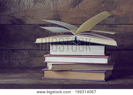 Old books on the table. A stack of books and open book on top.